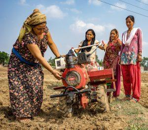 Women test a mini tiller for direct seeding of maize on farmland in Ramghat, Surkhet district, Nepal.